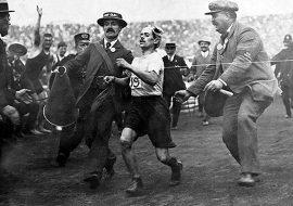 Dorando Pietri sendo ajudado na linha de chegada por fiscais da prova para ficar em primeiro lugar na maratona de 1908.